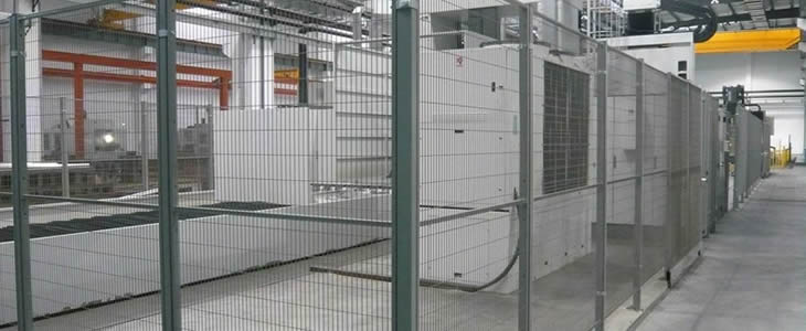 A white machine is surrounded by wire mesh partitions with dark green powder coated surface.