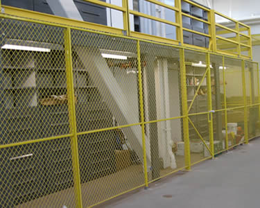 Yellow heavy duty wire mesh partition with extra height and reinforcement on the door.